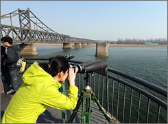 A woman uses binoculars April 5 for a glimpse of North Korea from the edge of the Yalu River bridge, also known as the Broken Bridge, on the Chinese side in Dandong.