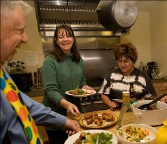 From left, neighbors Henry Kroll, DeAnne Butterfield and Gayla Oglesby share a meal in the community kitchen at Silver Sage Village in Boulder, Colo. Residents cook a meal together twice a week.