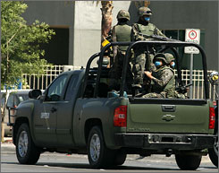 Mexican soldiers wearing protective masks patrol a street in Juarez, Mexico, on Wednesday.