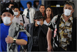 Travelers wear face masks to protect themselves from swine flu as they arrive at Los Angeles International Airport on Wednesday from Mexico City. Vice President Biden is nixing the idea of closing the United States' border with Mexico as a way to prevent the spread of the illness.