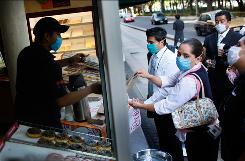 A vendor and his customers wear masks at a coffee and doughnut stand Thursday in Mexico City. President Felipe Calderon has ordered a five-day quarantine that begins today.