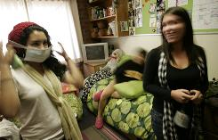 Friends watch Melanie Peinado, 18, left, a Long Beach State freshmen, put on a mask in her dorm room in Long Beach, Calif., Wednesday. The city says a probable case of swine flu has been found in a local college student.