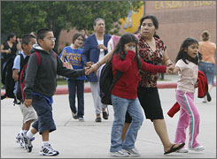 "Families leave the E.A. ""Squatty"" Lyons Elementary School in Houston on Thursday."