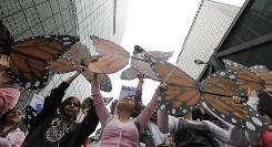 Protesters hold up butterfly wings during an immigration reform rally on Friday in Chicago. Activists chanted and carried banners demanding citizenship opportunities for illegal immigrants in the U.S. and an end to raids and deportations.