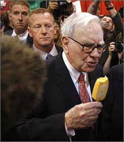 Billionaire financier and Berkshire Hathaway CEO Warren Buffett eats a Dairy Queen Vanilla Orange Bar as he walks through the company's annual shareholder meeting in Omaha Saturday. Berkshire owns Dairy Queen.