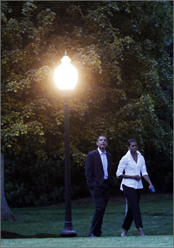 President Obama and first lady Michelle Obama walk along the South Lawn of the White House after returning from an evening dinner.