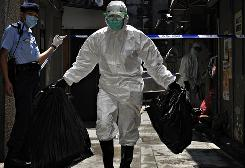 A health official removes items from a quarantined hotel in Hong Kong on Sunday. More than 300 guests and staff have been orderered to stay there for seven days after a Mexican guest tested positive for the swine flu virus.