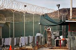 A guard talks to a Guantanamo detainee in the open yard in Camp 4 detention center on the U.S. Naval Base in Guantanamo Bay, Cuba. The House Democrats on Monday rebuffed the Obama administration's request for $50 million to relocate prisoners from the detention facility.