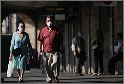 Officials in Mexico have announced they will reopen businesses on Wednesday, ending a five-day closure prompted by the swine flu outbreak there. Here, a couple wearing masks to ward off the new strain of flu walk past closed stores in Mexico City on Monday.