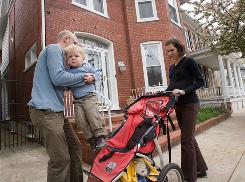 Silas picks up his son Emerson as Catherine holds the stroller. She's due to deliver their daughter in two weeks.
