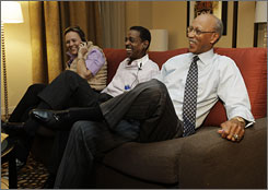 Former NBA basketball star Dave Bing, right, watches television waiting for election returns in Detroit.