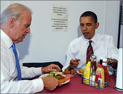 President Obama and Vice President Biden sit at a table with their cheeseburger lunch orders at Ray's Hell Burger in Arlington, Va.