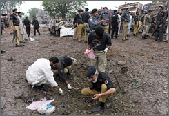 Pakistani police collect evidence after a suicide blast near Peshawar on Tuesday. A suicide car bomber rammed a Pakistani military vehicle, killing five people.