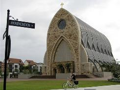A man bikes past the new church on the Ave Maria University campus in Immokalee, Fla. The recession has slowed construction, but billionaire Thomas Monaghan says his vision of a town and university steeped in conservative Catholic teaching will be built.