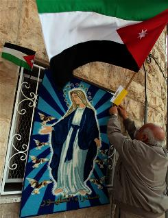 A Jordanian Christian hangs his national flag and the Vatican's flag next to a picture of the Virgin Mary in Madaba, Jordan. The pope begins his Holy Land on Friday in Jordan, then travels to Israel and the Palestinian territories May 11.