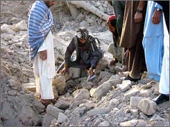 Afghan villagers on Tuesday sift through rubble left after a bombing by U.S. forces in Farah province, Afghanistan.