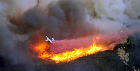 A plane drops fire retardant on Thursday over a ridge into Rattlesnake Canyon near Santa Barbara, Calif.