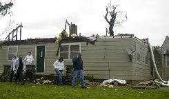 Friends and family members of Jim and Marsha Beggs try to contact them after inspecting damage of their home north of Carl Juction, Mo., which was hit by high winds on Friday. Many cities in southwest Missouri were without power after severe thunderstorms rocked the area.