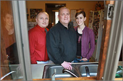 Richard Linnell, left, his husband, Gary Chalmers, and their 16-year-old daughter. Paige, stand in the kitchen window of their Whitinsville, Mass., home. Chalmers and Linnell, a married gay couple, say they didn't need the wedding to prove their commitment to one another, but they appreciate the added legal stability and the recognition they get from others.