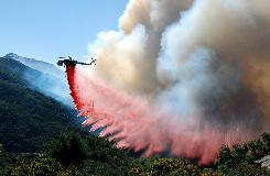 A helitanker drops fire retardant along mountain slopes in Santa Barbara, Ca., on Friday. The blaze is 30% contained.