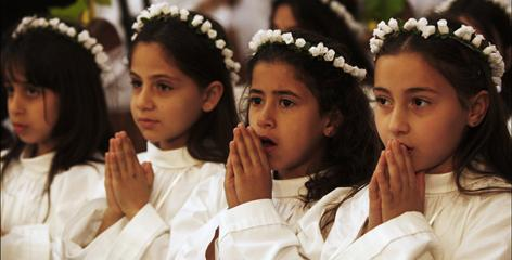 Palestinian Christian girls pray at Mass at the Church of the Nativity, traditionally believed to be the birthplace of Jesus Christ, in the West Bank city of Bethlehem on Sunday.