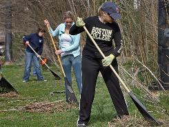 Beautifying Boston: Boston College alumna Jennifer Williams, class of 2000, foreground, wields a rake as part of a cleanup of Rogers Park. The alumni association organized simultaneous service events in cities across the USA last month.