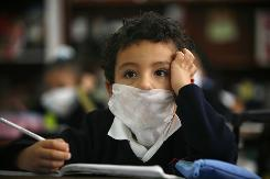 A boy wears as he attends his first day of school on Monday since it was shut down in the swine flu outbreak in Mexico City. A new study suggests that Mexicans  80% of whom have mixed European and Amerindian ancestry  could be genetically more susceptible to the H1N1 virus.