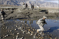 Afghan boys watch U.S. soldiers from the Alpha Company, 32nd Infatry Regiment cross a river in eastern Afghanistan.  President Obama is asking Congress for funds for the war effort in Afghanistan.