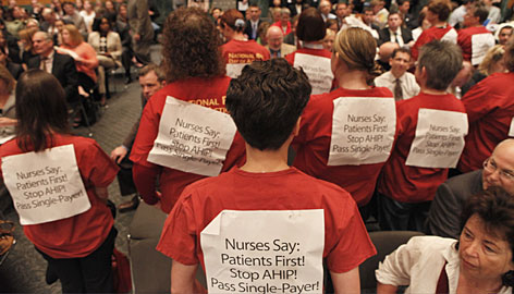 Nurses turn their backs on members of the Senate Finance Committee during Tuesday?s hearing on how to pay for a planned health care overhaul.