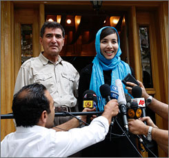 A smiling Roxana Saberi, flanked by her father, Reza Saberi, talks with the media outside her house in Tehran, Iran, on Tuesday, after her release from prison. An appeals court reduced the journalist's eight-year prison term to a two-year suspended sentence.
