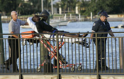 Fire Rescue personnel unload a survivor from a U.S. Coast Guard vessel on Wednesday from a dock in Phil Foster Park in Riviera Beach, Fla.