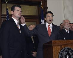 Texas Gov. Rick Perry, center, joins other state lawmakers in April as he discusses his support of a House resolution for Texas' sovereignty under the 10th Amendment of the U.S. Constitution.