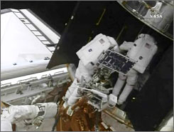 Astronaut Michael Good, on the shuttle's robotic arm, works with Mike Massimino work on fixing the Hubble's spectrograph, a task compared to performing brain surgery.