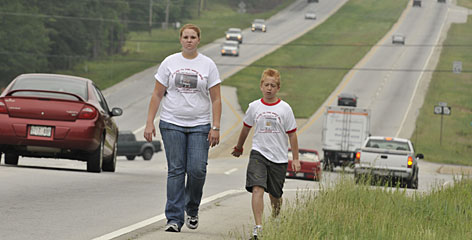 Zach Bonner, 11, walks down U.S. 78, in Monroe, Ga., with his sister Kelley, 21.