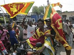 Sri Lankans hold national flags as they celebrate the victory of the military over Tamil Tiger rebels in Colombo on Monday. Sri Lanka declared it had crushed the final resistance of the Tamil Tigers, killing rebel chief Velupillai Prabhakaran.