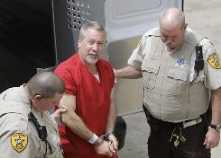 Former police officer Drew Peterson, center, was arraigned Monday on first-degree murder charges in the 2004 drowning death of his third wife, Kathleen Savio.