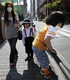 A family leaves Nisitenma elementary school in Osaka, Japan, after it was closed May 18 among 2,000 others in attempts to slow the spread of H1N1 virus.