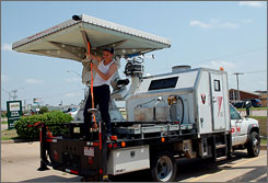 Isaac Lutz makes last-minute adjustments to a Doppler on Wheels vehicle Friday in Enid, Okla. The vehicle, one of several with Doppler radar on board, can do rapid radar scans of storms as they move across the Great Plains.
