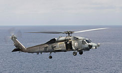 A U.S. Navy Seahawk helicopter approaches the flight deck of the aircraft carrier USS Abraham Lincoln off the coast of Indonesia in this Jan 13, 2005 file photo. The Coast Guard says a Navy helicopter, similar to the one shown, crashed into the ocean 13 miles south of San Diego near the Coronado Islands shortly before midnight Tuesday.