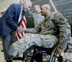 Master Sgt. Daniel Robles shakes hands with philanthropist Arnold Fisher after a ceremony Jan. 28 in which he received the Purple Heart at the Center for the Intrepid at Fort Sam Houston in San Antonio.