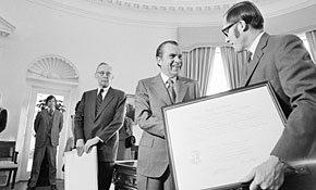 Then-president Richard Nixon gives a framed commission to William Rehnquist, right, after handing one to Lewis Powell, left, in 1971.