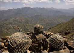 Pakistani Army soldiers guard a defensive position on a former Taliban base overlooking the Swat Valley Friday.