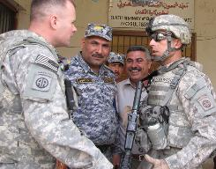 U.S. Army Spc. Forat Aldawoodi, right, originally from Iraq, translates a conversation between an Army officer and an Iraqi police commander.