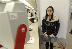 Diana Kim, of Fairfax, Va., is sure not to smile as she gets her driver's license photo taken. Virginia uses face-recognition software that won't allow for smiles on IDs.