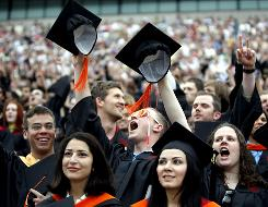 Students cheer during the University of Oklahoma graduation ceremonies in May. Some state legislatures are considering policies that would link college funding to student graduation rates.