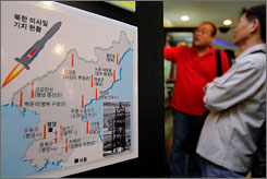 Visitors at the border village of Paju, South Korea, study a sign offering details about North Korea's missiles Tuesday. North Korea test-fired two short-range missiles.