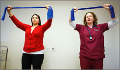 Pregnant mom Elena Nieves, left, gets instruction from exercise physiologist Lindsey Hanna at Northwestern Memorial Hospital in Chicago. A new national report says that women and their doctors must focus more on keeping down weight gain during and after pregnancy.