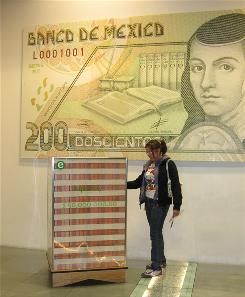 A visitor looks at a stack of 50 million pesos ($4 million) in phony 100-peso bills at the Interactive Museum of Economics in Mexico City on May 21. Behind her is an enlarged 200-peso note.