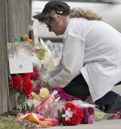A woman who declined to be identified pauses Monday before a memorial of flowers outside the Dr. George Tiller's Women's Health Care clinic in Wichita.