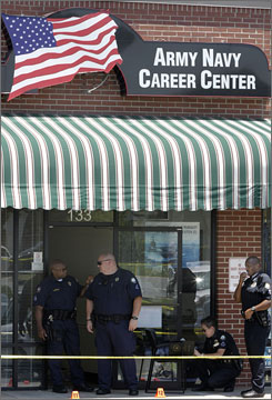 Little Rock police inspect the scene of a shooting outside a military recruitment office that left one soldier dead and another wounded Monday.